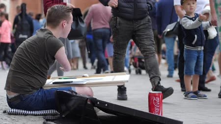 inwalida : Wroclaw, Poland 12 May 2018: artist crippled men draws paintings and good people throw money into tin on open air in Wroclaw, 12 May 2018.