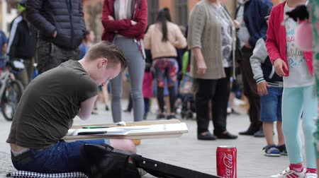 ón : Wroclaw, Poland 12 May 2018: contemporary art, handicapped male creates paintings and generous passers throw money into jar at town square in Wroclaw, 12 May 2018.