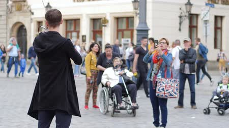 com cordas : Wroclaw, Poland 12 May 2018: street creativity, musician is playing on violin on town square for viewers in Wroclaw, 12 May 2018.