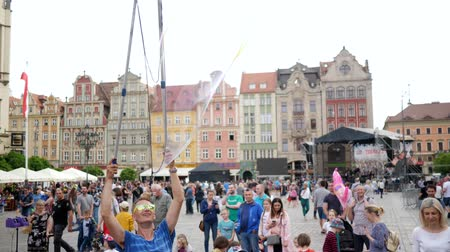 hůlky : Wroclaw, Poland 12 May 2018: street entertainment, men is making big soap bubble on air outdoors for people in city on weekends in Wroclaw, 12 May 2018.