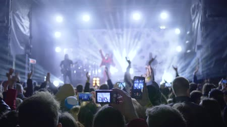 película de filme : Kherson, Ukraine 30 March 2018: live music, fans clap and record video on smartphone during performance of rock show on stage in searchlight lighting in Kherson, 30 March 2018.