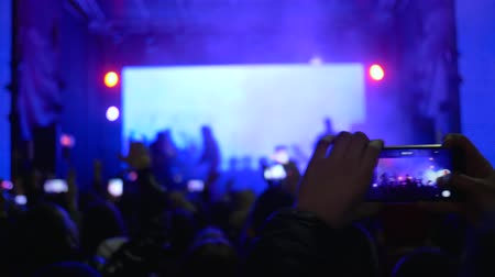 película de filme : crowd of fans with smartphone in hands enjoy live music at concert in vivid stage lights at night