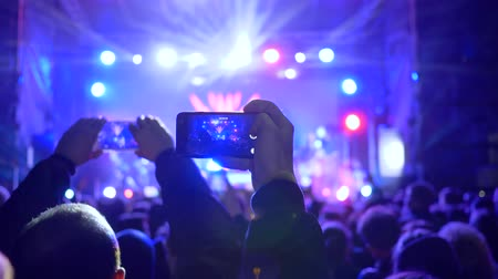 floodlight : crowd of youth with gadget in hands at rock concert in floodlight lighting at night Stock Footage