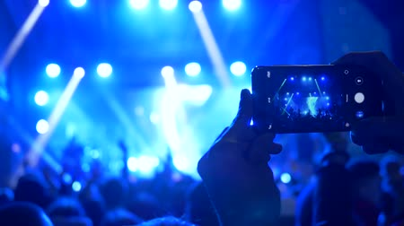 searchlight : rock concert, audience shoot on mobile phone performing of musical group on brightly illumination at night Stock Footage