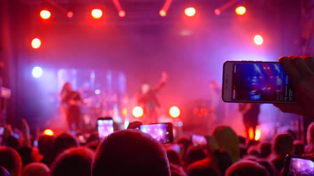 searchlight : rock festival, many people with gadget in hands make video recording at concert in floodlight lighting