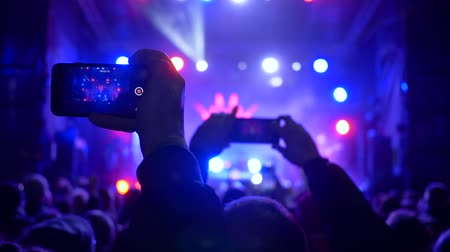 searchlight : live music, crowd of fans with cell phone in hands at rock concert in spotlight lighting at night