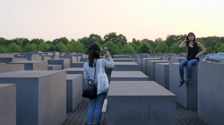 еврей : Berlin, Germany 15 May 2018: girl tourist takes pictures of a girlfriend who sits on gray slab, Holocaust Memorial in Berlin, 15 May 2018.