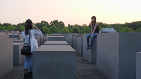 genocide : Berlin, Germany 15 May 2018: tourist with mobile phone in hand takes pictures of a girlfriend who sits on gray slab, Holocaust Memorial in Berlin, 15 May 2018.