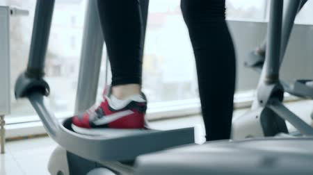 red shoes : cardio training, foot of human go on Elliptical trainers in sports center close-up