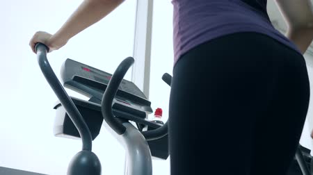 elliptical : sports girl engaged in fitness, women ass close-up bottom view