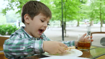 come : unhealthy food, little boy drinks apple juice from a glass and eats a slice of pizza in cafe in the open air Vídeos