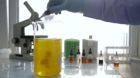 artigos de vidro : Scientists conducts chemical reaction in large glass with reagents in modern laboratory close-up on unfocused background Stock Footage