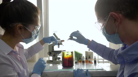 lab employee : science researcher make chemical solution with color liquids in chemical laboratory in bright lighting