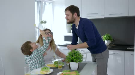 segurelha : happy family lunch, kid feeds father delicious food and mother laughs sitting at table indoors Stock Footage