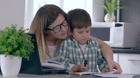 telefon : single mother is working at home on computer talking on telephone and taking care of son at same time