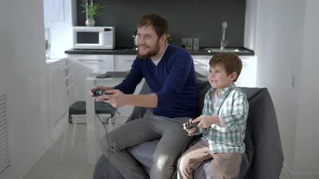 petite : video games, Men with son play with game controller into hands at home in holiday
