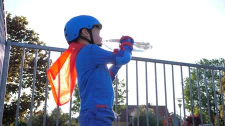 ustalık : sport children drinking water, boy into superhero costume with cooling beverage in plastic container on open air in backlight close-up