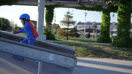 ustalık : sporting competition, kid into roller in helmet gaining speed at Skate Park outdoors Stok Video