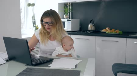 nanny : motherhood, mom with a baby in her arms scolds her son who interferes with working at home Stock Footage