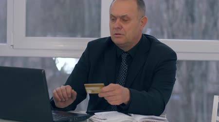 kart : pensioner purchase online, businessman with credit card in one hand uses a laptop in a modern office