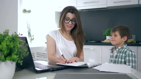 small pen : successful business at home, young mom in glasses makes notes in notebook sitting on kitchen and then happily hugs her son