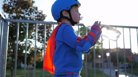 закалки : drinking water, Rollerblading child in helmet with plastic bottle into hand outdoors in backlight Стоковые видеозаписи