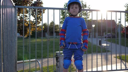 ustalık : happy child winner, boy in roller skates and helmet raises hands up on rollerdrome outdoors in sunlight Stok Video