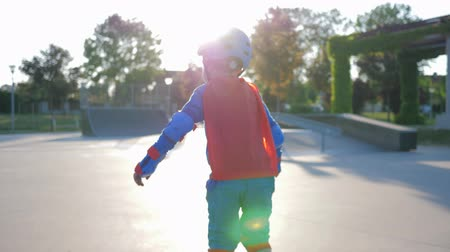 fearless : roller sports, active child into helmet ride to asphalt road in Skate Park outdoors in backlight