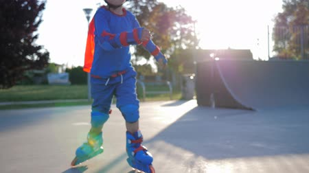 ustalık : Rollerblading child is playing sports at Skate Park on open air close-up in unfocused background