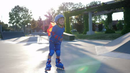 ustalık : Skate Park, fearless child into superhero costume rollerblading on playground on open air in an unfocused Stok Video
