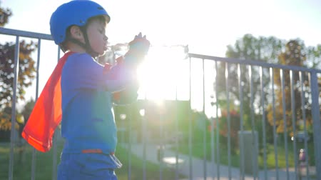 закалки : sports child in helmet and rollers drinks pure water from plastic bottle outdoors in backlight