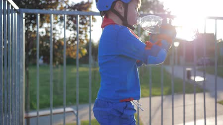 колено : thirst quenching, kid drinks mineral water from plastic bottle at Skate Park in sunlight