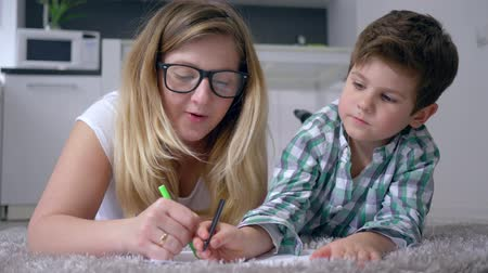 mama : home education, mum with son draw pictures with colored markers on white sheet lying on floor at home in vacation close-up