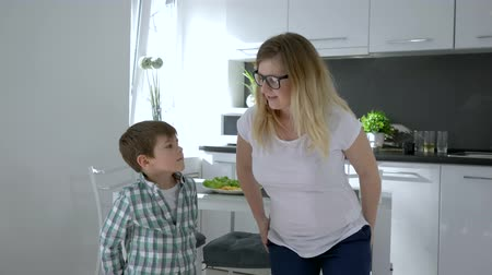 mama : modern dances, mother in glasses teaches son dance movements at home in kitchen on holiday