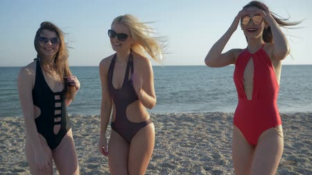 fürdés : vacation at sea, girls in swimsuits are having fun together on the sandy beach at summer Stock mozgókép