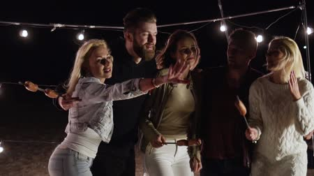 špejle : young friends on a picnic dance and have fun on a night beach in slow motion