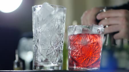 desfocado : person pour out scotch in glass with ice and near is vivid ready drink close-up
