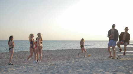 купальный костюм : beach games, girls play volleyball in front of guys friends on seaside in summer trip