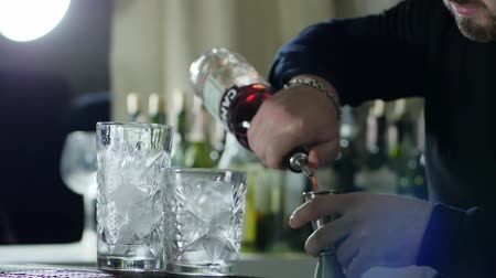 desfocado : man bartender slow pours rum from bottle into jigger behind bar with clean glasses with ice close-up