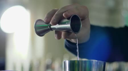 desfocado : man arms holds jigger and slow pours whiskey into shaker close-up on an unfocused background
