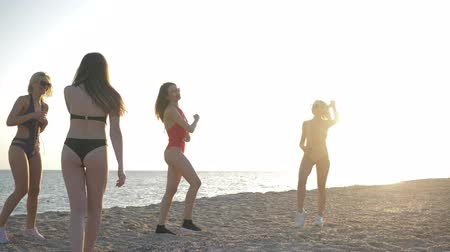 beach volleyball : beach volleyball, young girls in swimsuits play with ball on sand on backdrop of sea sunset at summer vacation
