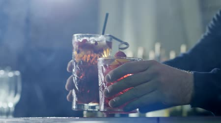 desfocado : hands of person exhibit beautiful freshly prepared drinks with berries on foreground in light haze Stock Footage