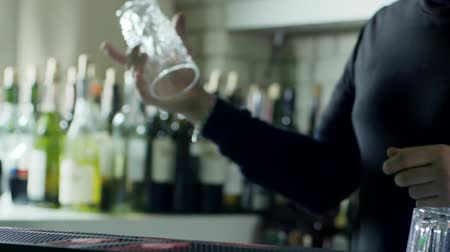 desfocado : bartender makes trick with empty glass and puts it on bar counter close-up on background of bottles