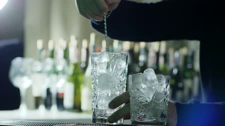 desfocado : bar spoon into hands of man mixes ice cubes in large transparent glass close-up Stock Footage