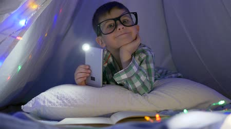 do interior : portrait of boy wearing glasses dreams and lying in the tepee with a phone in hands