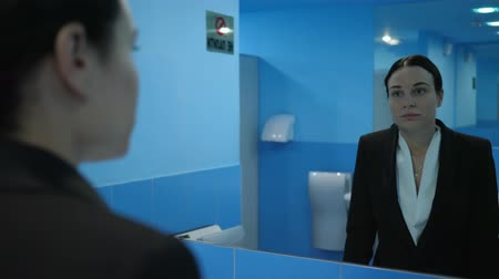 público : offended girl in the public bathroom takes off her glasses and looks at herself in the mirror Vídeos