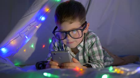 gizli : little smart boy with glasses watching video on mobile phone hiding in tent with garland at home close-up