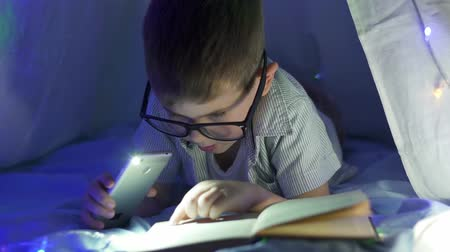 festoon : night reading, cute smart child in eyeglasses is see in magazine under flashlight under blanket at dark indoors close-up Stock Footage