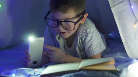 festoon : home education, happy smart boy into spectacles with flashlight reading fairy tale in tent In dark close-up