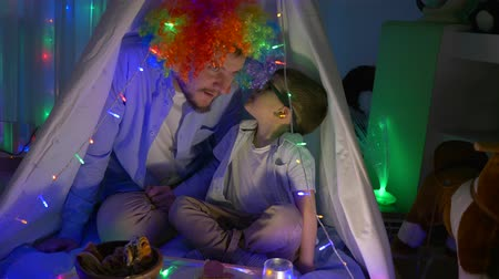 festoon : time of leisure, nice child tells secrets of merry father into wig sitting in teepee in evening at home